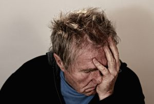 self blame aging worker man with hand on face