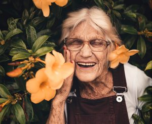 older woman in flowers smiling happiness after 50