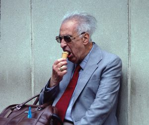 elderly man in suit with briefcase eating ice cream